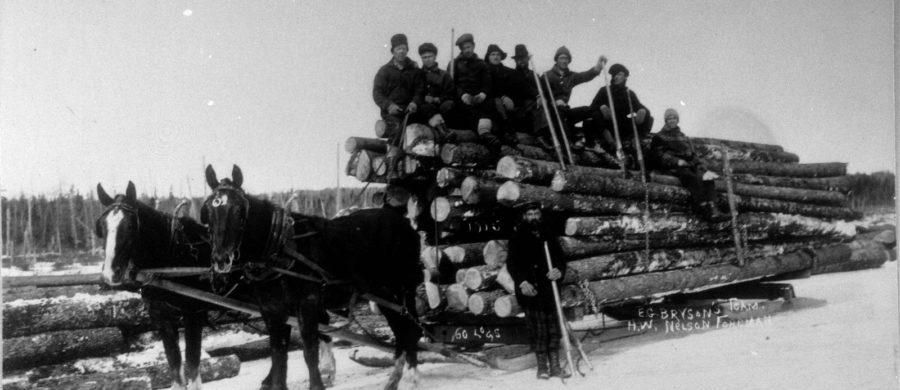 Lumbermen on top of horse drawn lumber cart.